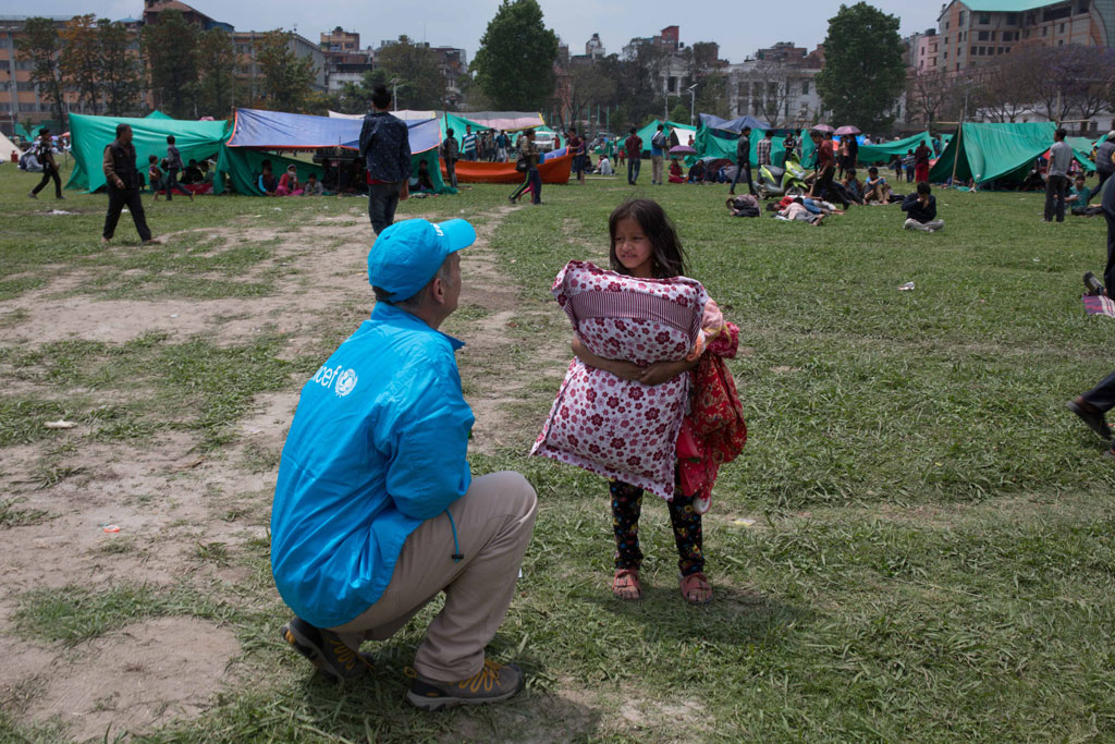 On 26 April 2015, a UNICEF worker speaks to a child seeking temporary shelter at a vacant field next to Nepal's army headquarters in Kathmandu following Nepal's massive earthquake. In April 2015, UNICEF is mobilizing an urgent response to meet the needs of children affected by the earthquake in Nepal on 25 April.  With children accounting for half the country's population, UNICEF fears the disaster, which is reported to have already killed hundreds of people, will have a severe impact on children. UNICEF has prepositioned supplies, including water purification tablets, hygiene kits, tarpaulins and nutrition supplies, and is working with government and other partners to meet children's immediate needs in the areas of water and sanitation, child protection, health and nutrition.