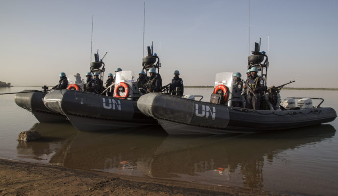 UN peacekeepers from Bangladesh stand on boats during a river patrol in the Niger river in Ansongo, in eastern Mali.